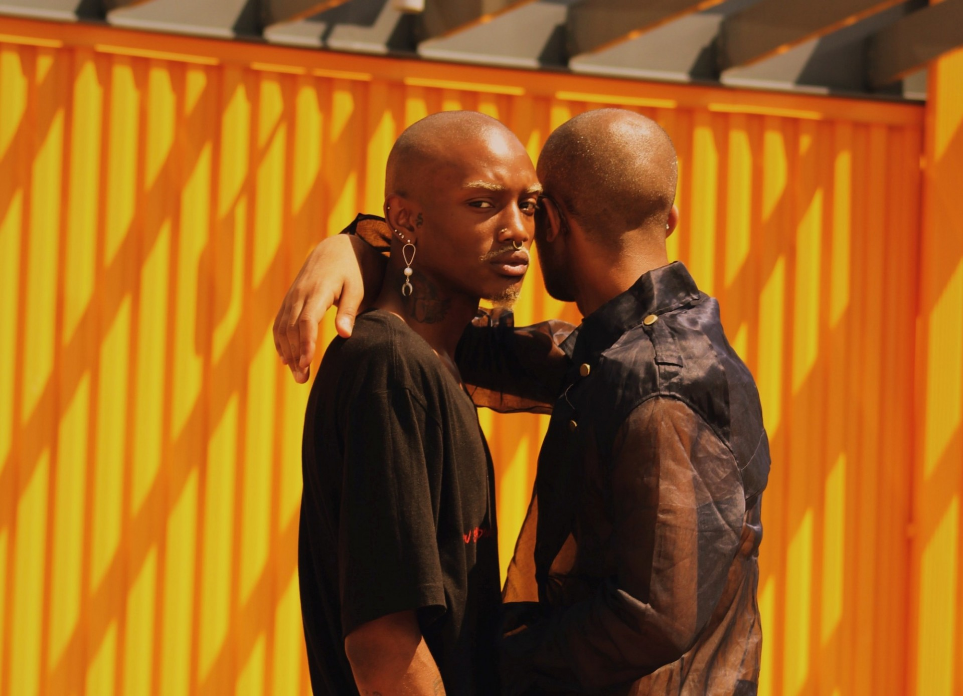 a couple (two Black men) standing and hugging