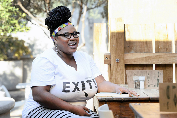 Photo of Grizelda Grootboom laughing at a table outside with an Exit t-shirt