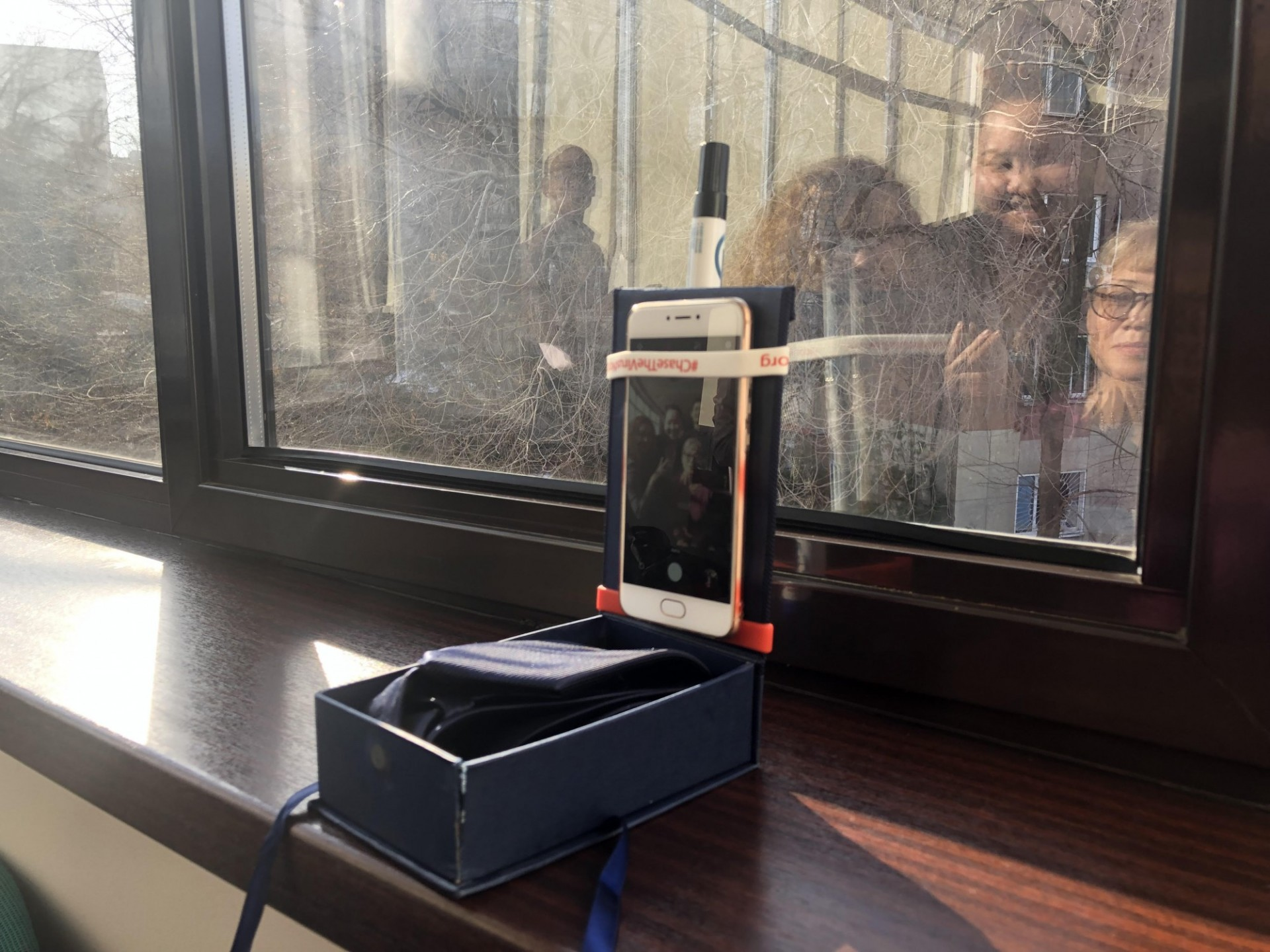 a smartphone taped to a box and window as a stand