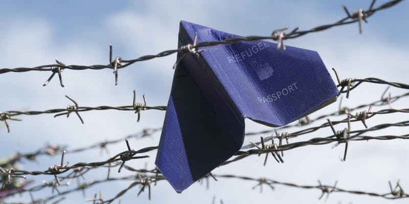 refugee passport stuck in barbed wire